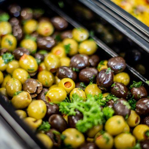 Närbild av kantin fylld med gröna och svarta oliver med lite persilja ovanpå