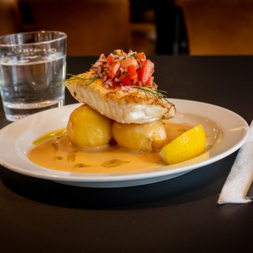 Aptitlig tallrik med fisk och potatis serverad på ett svart bord bredvid glas vatten och bestick