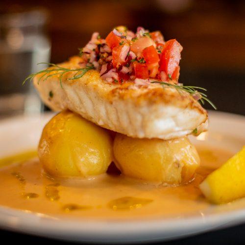 Fotografiskt effektfull bild på fisk som ligger ovanpå potatis. I bakgrunden ett glas vatten, ur fokus