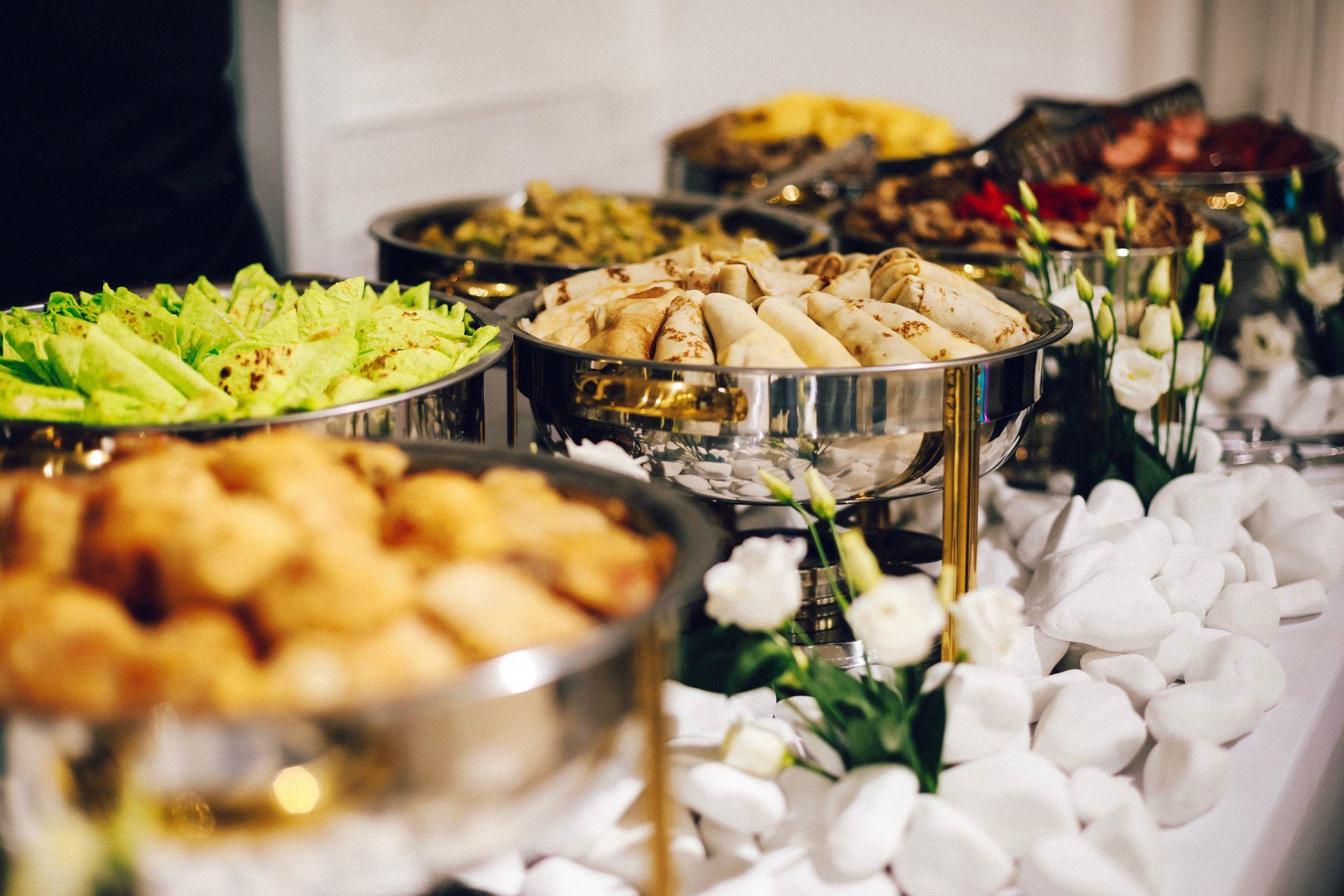Snyggt upplagd buffébord och 6 skålar med olika innehåll. Allt från vårrullar och pastablandningar till sallader och friterat kött